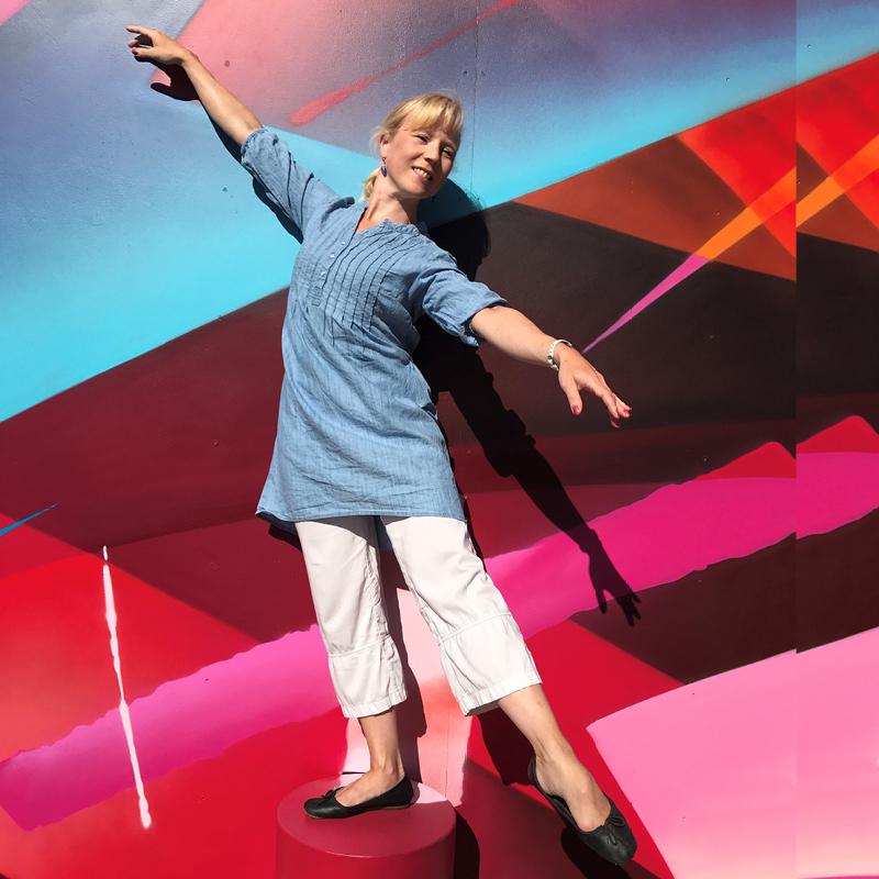 Jaana Reinikka tanssii värikkään taustan edessä.