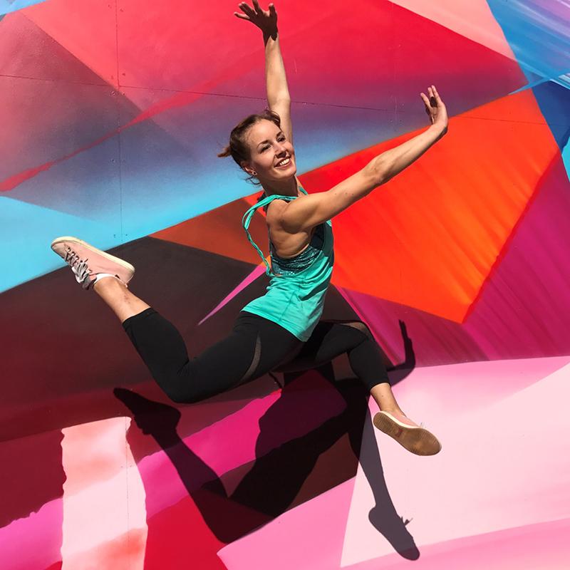 Tanssinopettaja Viivi Virtanen hyppää värikkään taustan edessä.